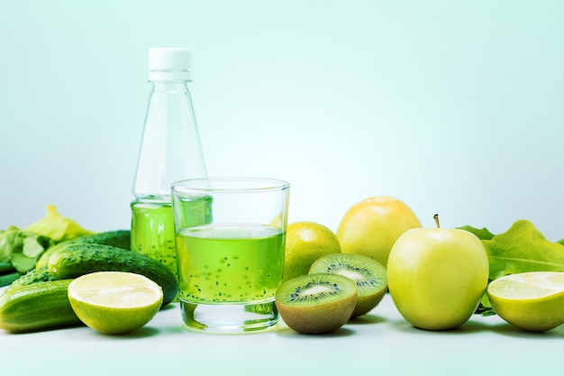 Frisches grünes obst, gemüse und grüner smoothie im glas auf dem tisch. detox-, diät- oder gesundes lebensmittelkonzept.