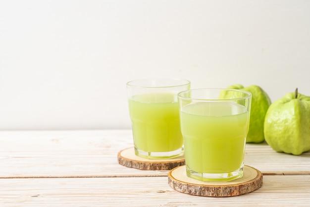 Frisches guavensaftglas mit frischen guavenfrüchten auf holztisch