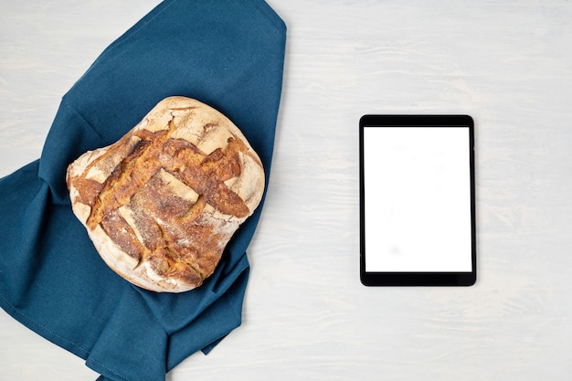 Frisches hausgemachtes bio-brot und notizblock mit platz zum kopieren. gesundes essen, kochanwendung, online-brotrezeptkonzept. modell, draufsicht, flache lage