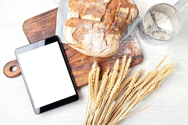 Frisches hausgemachtes bio-brot und notizblock mit platz zum kopieren. gesundes essen, kochanwendung, online-brotrezeptkonzept.