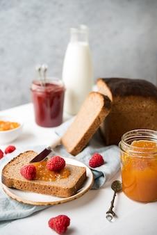 Frisches hausgemachtes brot mit marmelade und milch, hausgemachtes einfaches essen, heller hintergrund