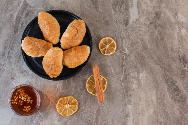 Frisches hausgemachtes croissant mit getrockneten zitronenscheiben.