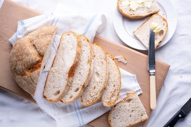 Frisches hausgemachtes gebackenes brot und geschnittenes brot auf rustikalem weißem holztisch.