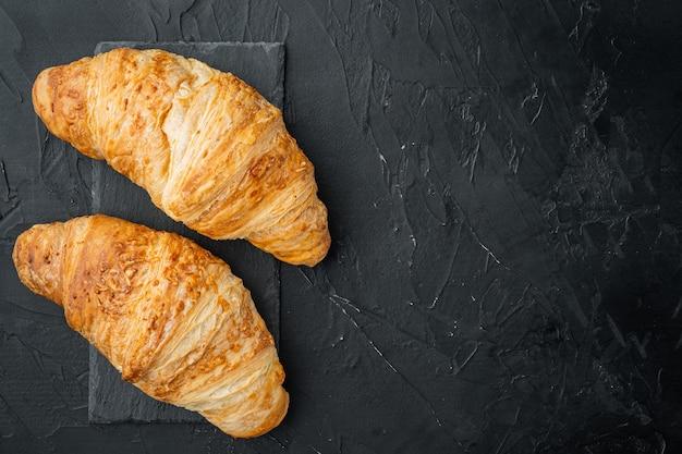 Frisches hausgemachtes gebackenes goldbraunes croissant-set, auf schwarzem steinhintergrund, draufsicht flach, mit kopierraum für text