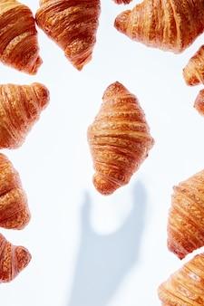 Frisches hausgemachtes köstliches croissant mit schatten von hand auf hellem hintergrund, platz für text. lebensmittelrahmen. kontinentales frühstückskonzept.