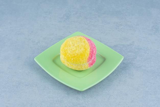 Frisches hausgemachtes plätzchen auf pfirsichform über grüner platte.