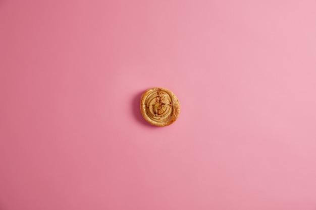 Frisches hausgemachtes spiralbrötchen für ihr leckeres frühstück zur befriedigung von naschkatzen. appetitlich leckeres gebäck mit vielen kalorien, von oben auf rosa hintergrund photorgaphiert. aromatisches dessert