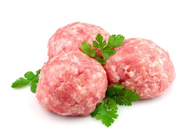 Frisches haushackfleisch mit grün auf weißem hintergrund