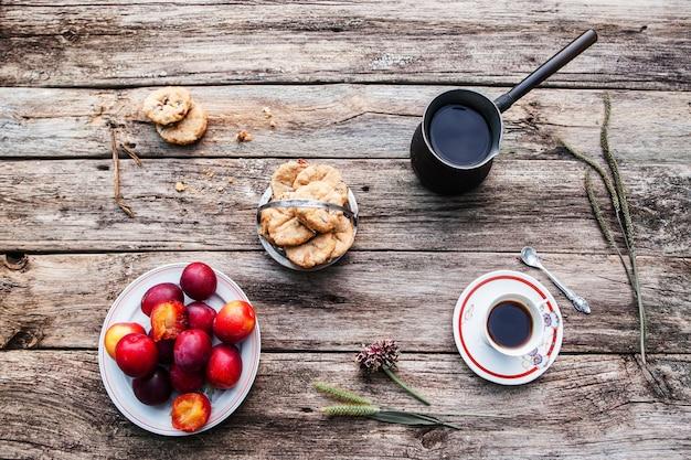 Frisches herbstfrühstück für eine, flache lage. tasse und kanne kaffee mit keksen und pflaumen draufsicht. einsamkeit, ruhe vom gemeinschaftskonzept