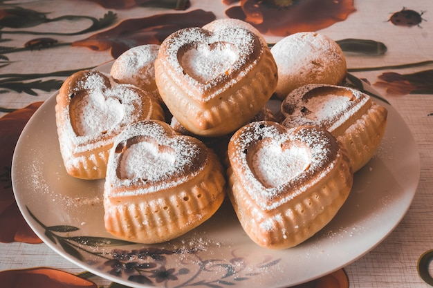Frisches herzförmiges gebäck auf einem mit vanille bestreuten teller.