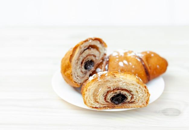 Frisches hörnchen mit schokolade auf weißem holz