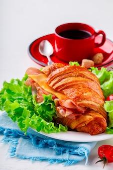 Frisches hörnchen-sandwich mit schinken, käse, kirschtomaten
