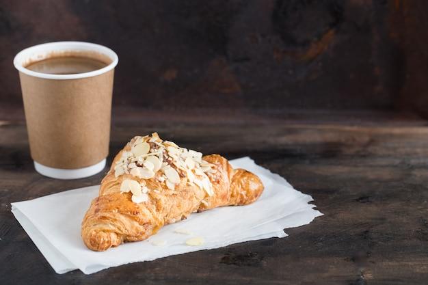 Frisches hörnchen und kaffee in einer papierschale auf dunkelheit