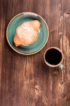 Frisches hörnchen und tasse schwarzen kaffee