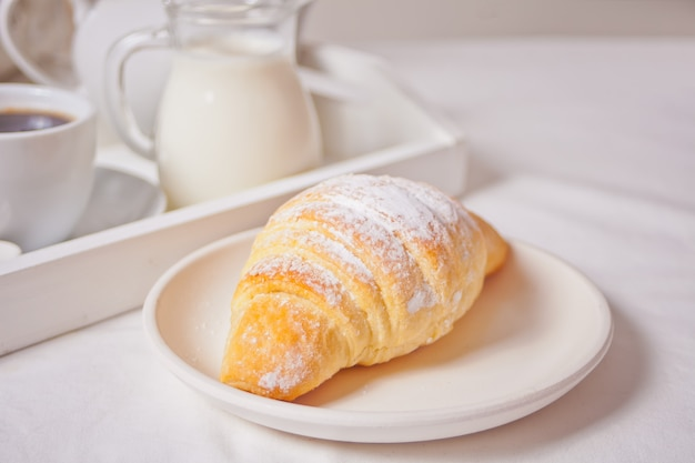 Frisches hörnchenbrötchen auf der weißen platte mit tasse kaffee, glas milch