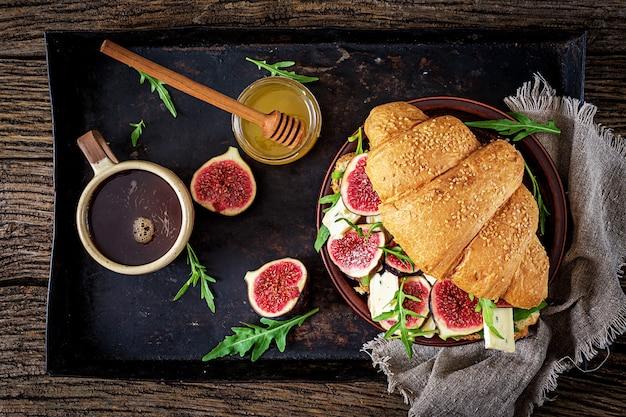 Frisches hörnchensandwich mit briekäse arugula und feigen. leckeres frühstück. leckeres essen. flach liegen. ansicht von oben