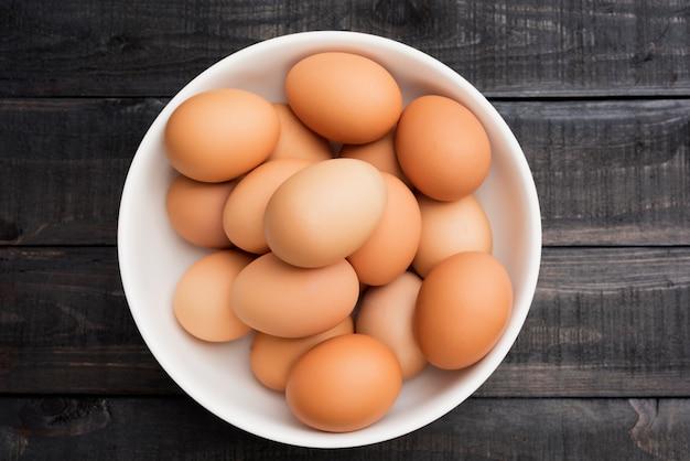 Frisches hühnerei in der weißen schüssel auf schwarzem holztisch