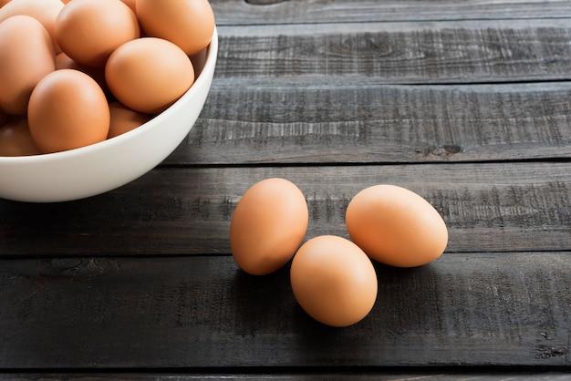 Frisches hühnerei in weißer schüssel und 3 hühnerei außen auf schwarzem holztisch