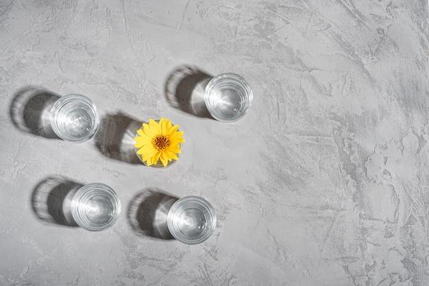 Frisches klares wassergetränk mit gelber blume im glas auf beton
