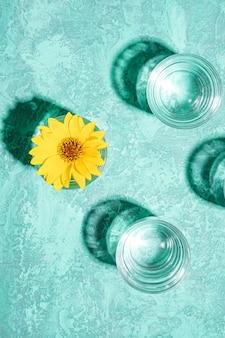Frisches klares wassergetränk mit gelber blume im glas auf türkis