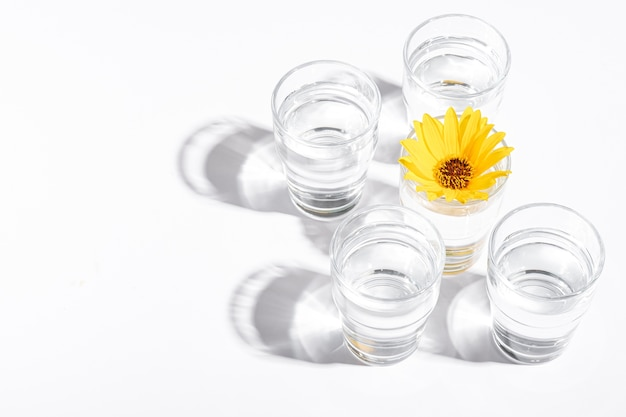 Frisches klares wassergetränk mit gelber blume im glas auf weiß. draufsicht