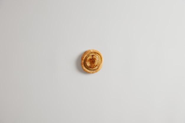 Frisches klebriges süßes zimtbrötchen mit aromatischem, angenehmem geruch und köstlichem geschmack. gebackenes hausgemachtes gebäck zum frühstück mit tee oder kaffee. leckerer ganzer wirbel. süßwarenkonzept