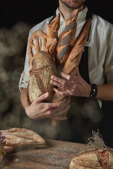 Frisches knuspriges brot in den händen eines bäckers auf dunklem hintergrund nahe einem holztisch mit rundem brot