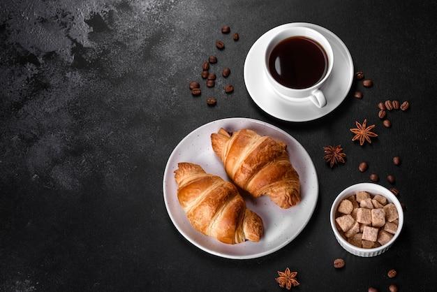 Frisches knuspriges köstliches französisches croissant mit einer tasse duftendem kaffee auf einem dunklen betonhintergrund. belebendes frühstück
