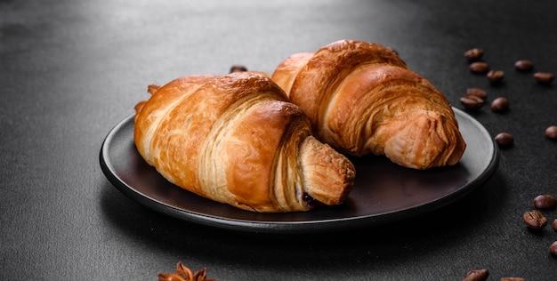Frisches, knuspriges, köstliches französisches croissant mit einer tasse duftendem kaffee. belebendes frühstück