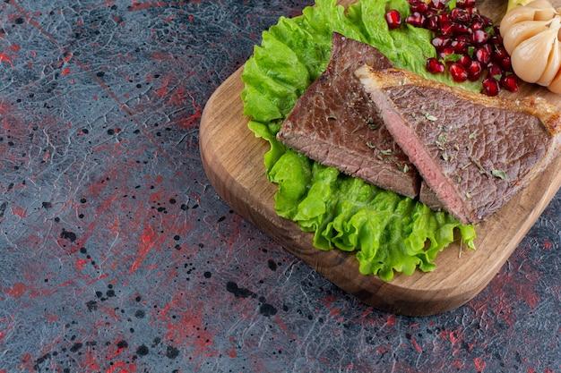 Frisches köstliches saftiges steak mit salatsalat auf holzschneidebrett gelegt.