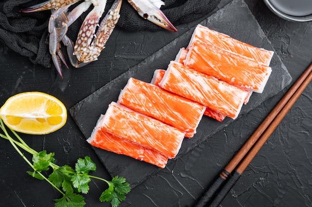 Frisches krabbenfleisch-stock-surimi mit blauem schwimmkrabbensatz, auf steinbrett, auf schwarzem hintergrund
