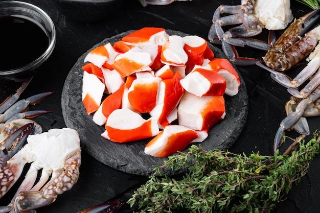 Frisches krabbenfleisch surimi mit blauem schwimmkrabbensatz, auf schwarzem hintergrund