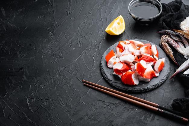 Frisches krabbenfleisch surimi mit blauem schwimmkrabbensatz, auf steinbrett, auf schwarzem hintergrund, mit copyspace und raum für text