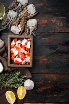 Frisches krabbenfleisch surimi mit blauem schwimmkrabbensatz, in der holzkiste, auf dunklem hölzernem hintergrund, draufsicht flache lage, mit copyspace und raum für text
