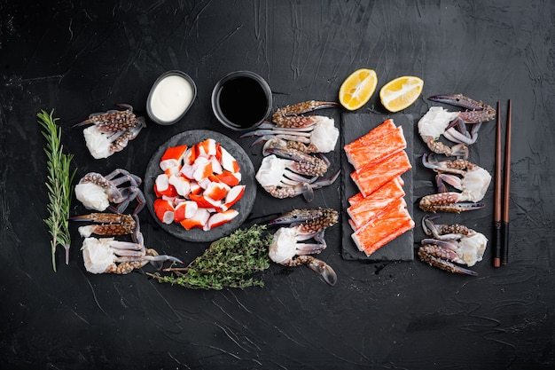 Frisches krabbenfleisch und stangen surimi mit blauem schwimmkrabbensatz, auf schwarzem hintergrund, draufsicht flach legen