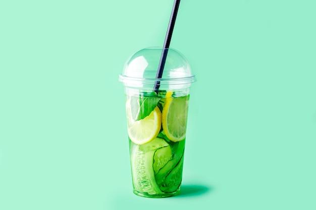 Frisches kühles entgiftungsgetränk mit gurke, zitrone und basilikum im plastikbecher auf grün