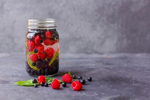 Frisches kühles entgiftungsgetränk mit himbeeren, blaubeeren und kiwi im einmachglasbecher. limonade in einem glas mit minze. konzept der richtigen ernährung und gesunden ernährung.