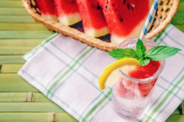 Frisches kühles sommergetränk mit wassermelonenscheiben, minze und zitrone auf einem hölzernen hintergrund