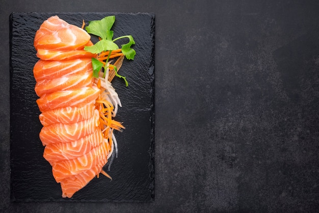Frisches lachs-sashimi-filet mit karotte, radieschenscheibe und sellerie in schwarzem schiefer