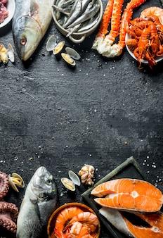 Frisches lachssteak mit meeresfrüchten. auf schwarzem rustikalem hintergrund
