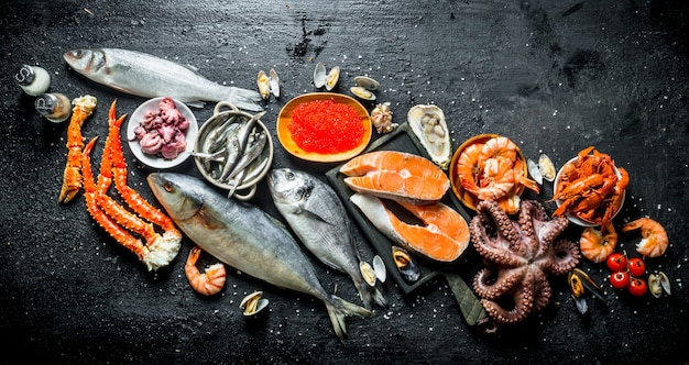 Frisches lachssteak mit tintenfisch, kaviar, garnelen und krebsen auf schwarzem rustikalem tisch