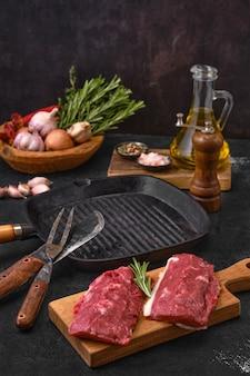 Frisches lamm- oder kalbsprimesteak auf schneidebrett mit kräutern, gewürzen, knoblauch und zwiebeln