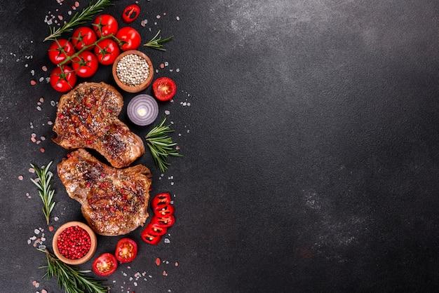 Frisches leckeres saftiges steak auf den knochen mit gemüse und gewürzen. saftiger schweinefleischsteakgrill auf dunklem tisch