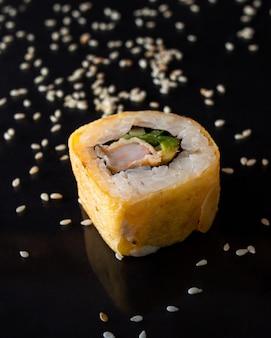 Frisches leckeres sushi mit avocado, cremigem käse, lachs und isoliert auf schwarz mit reflexion