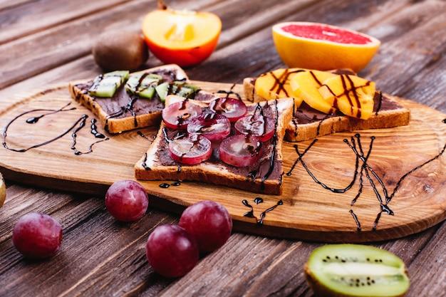 Frisches, leckeres und gesundes essen. mittag- oder frühstücksideen. brot mit schokoladenbutter, traube