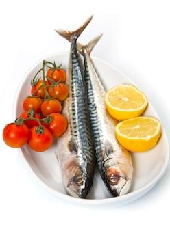 Frisches meckerel auf weißem teller mit zitrone und kleinen tomaten