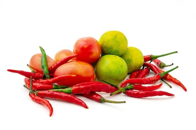 Frisches mischgemüse lokalisiert auf einem weißen hintergrund, rote chilis, tomate und grüne zitrone. gruppe thailändische gewürze und gemüse.