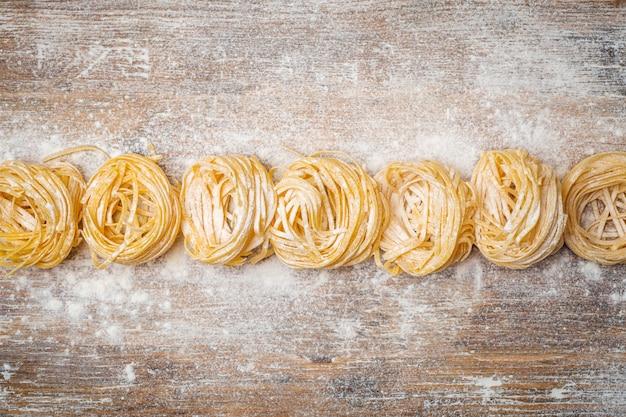 Frisches nudelessen. hausgemachte italienische pasta gekocht auf einem holztisch im rustikalen stil, dekoriert mit ei und mehl.