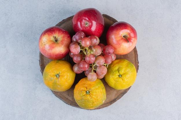 Frisches obst der saison. roter apfel und traube mit mandarine.