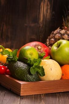 Frisches obst und gemüse in einem hölzernen behälter